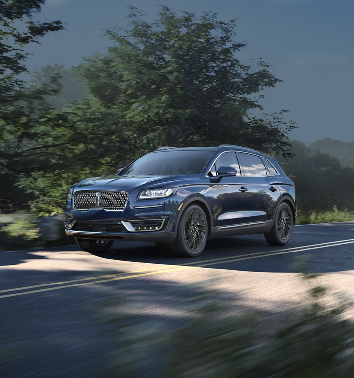 A 2020 Lincoln Nautilus is shown in the rhapsody blue colour being driven down a country road