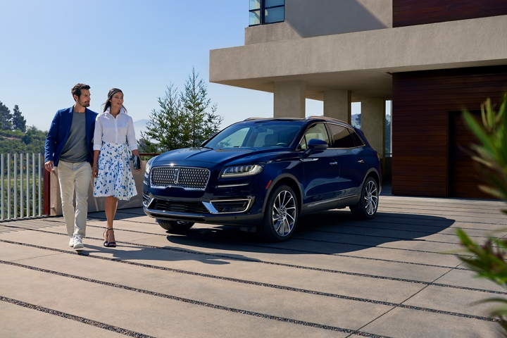 A 2020 Lincoln Nautilus shown in the Rhapsody Blue exterior colour is parked in the driveway of a modern hillside home