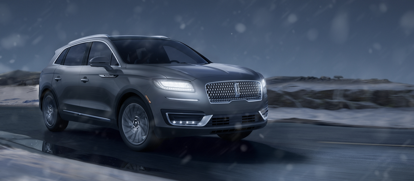 A 2020 Lincoln Nautilus is shown being driven at night with the L E D headlamps brightly illuminated