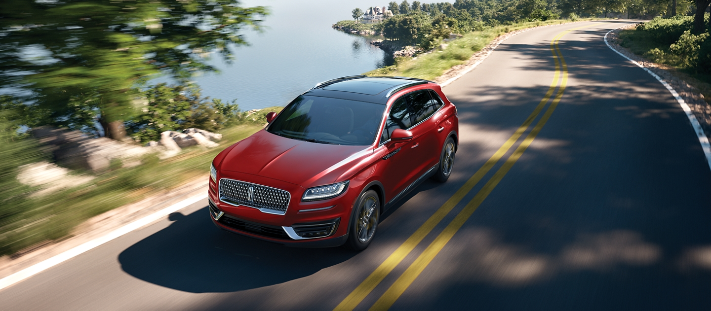 A 2020 Lincoln Nautilus is shown in the Red Carpet exterior colour as it is being driven along a coastal roadway
