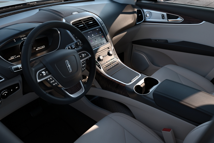 The steering wheel and centre stack of a 2020 Lincoln Nautilus are shown as seen from the drivers point of view as they enter the vehicle