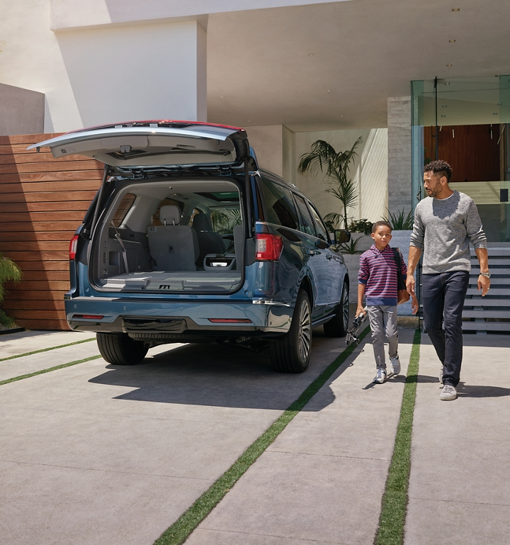 A father and son are shown approaching a Lincoln Navigator with the available Tiered Cargo Management System in the rear cargo area
