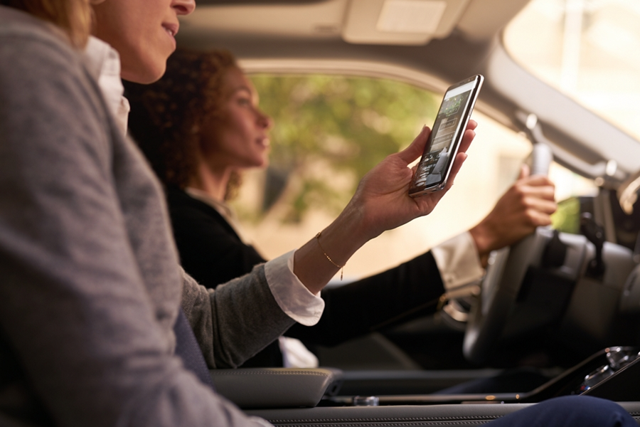 A passenger in a Lincoln Navigator is shown using a mobile device