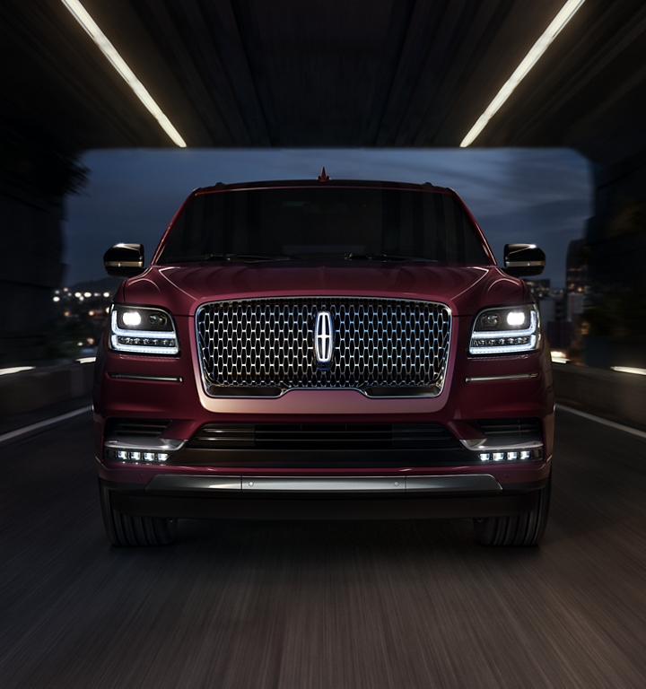A Lincoln Navigator is shown being driven with a large Lincoln Star logo with available illumination in the middle of the grille