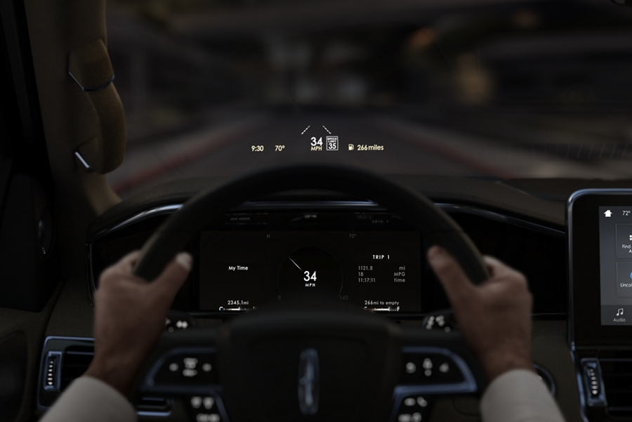 A pair of hands grip the steering wheel while the Head Up Display projects vital information on the windshield
