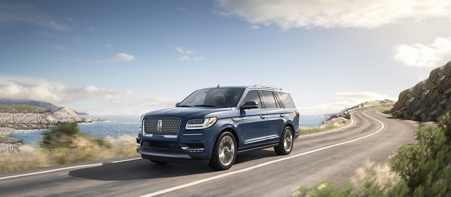 A Lincoln Navigator in the Blue Diamond Metallic exterior color is shown being driven on a water side road