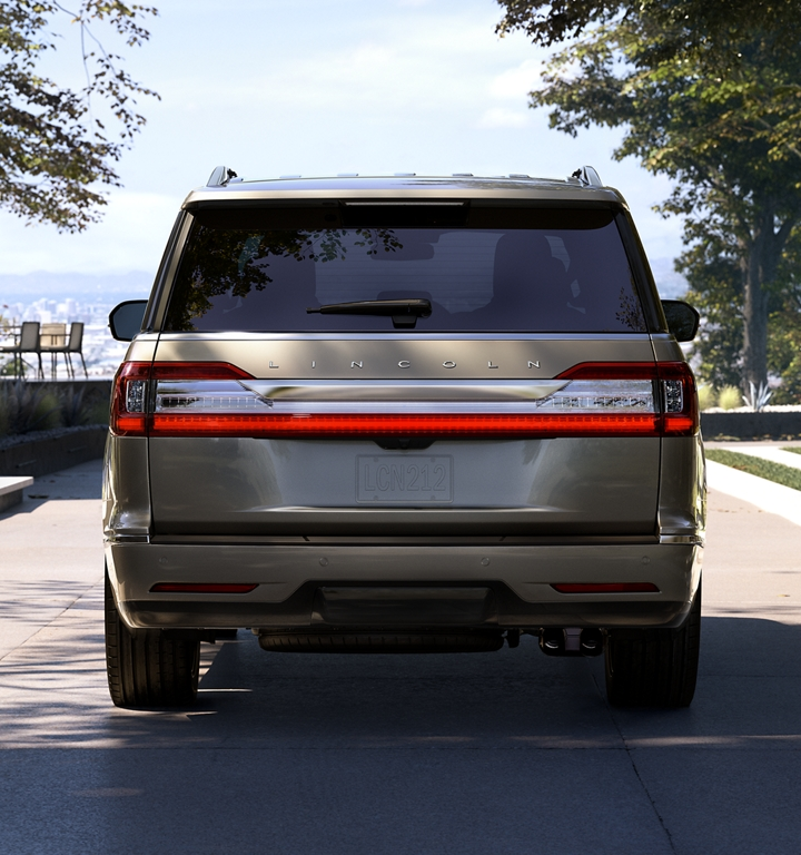 A Lincoln Navigator is shown coming to a stop in a driveway and being greeted by the family dog