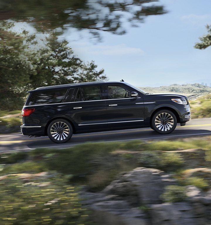 A Lincoln Navigator is shown being driven up a hill in the countryside