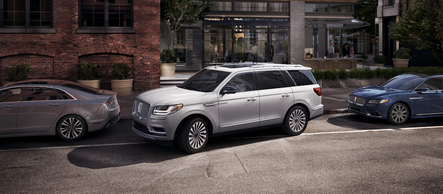 A Lincoln Navigator is shown being parallel parked to demonstrate the available enhanced active park assist system