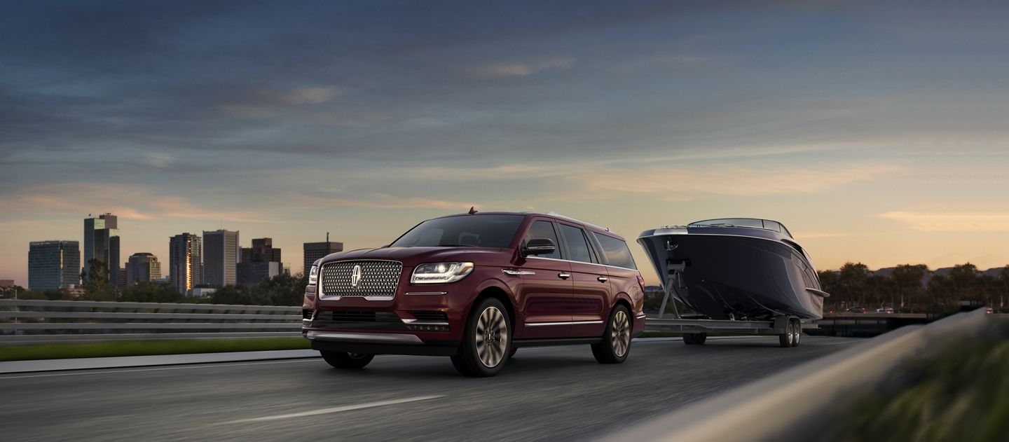 A 2018 Lincoln Navigator is shown with a large speedboat in tow