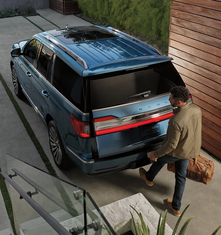 A man is shown kicking his foot under the rear bumper of a Lincoln Navigator to open the hands free rear lift gate