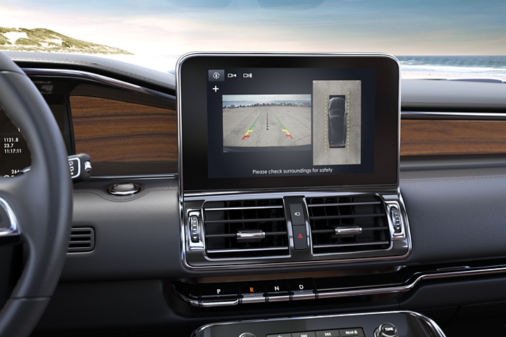A 2020 Lincoln Navigator is parked on a beach with the bright 10 inch L C D screen displaying the birds eye view of the 3 60 degree camera