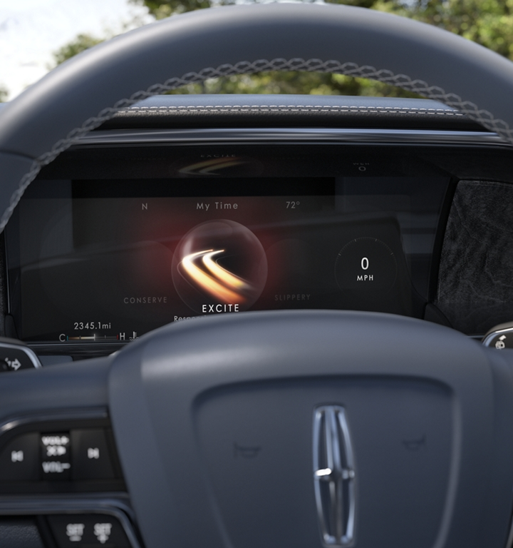 A bright swiping graphic representing the Excite drive mode illuminates the information screen behind the steering wheel with a soft blue glow