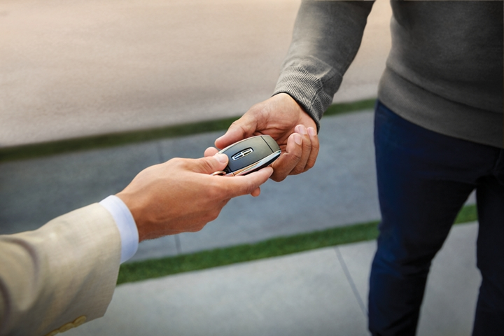 Two hands are shown exchanging a Lincoln key fob to demonstrate Lincoln Pickup and delivery