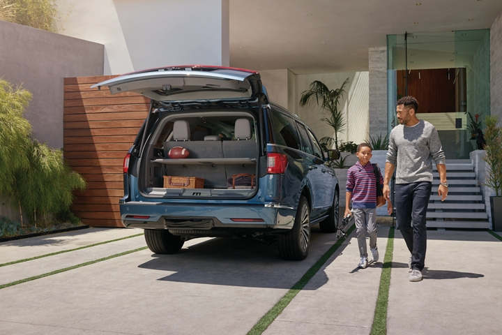 The open cargo area of a 2020 Lincoln Navigator shows off a shelving unit that separates sports cargo and bags as a man and boy approach the vehicle