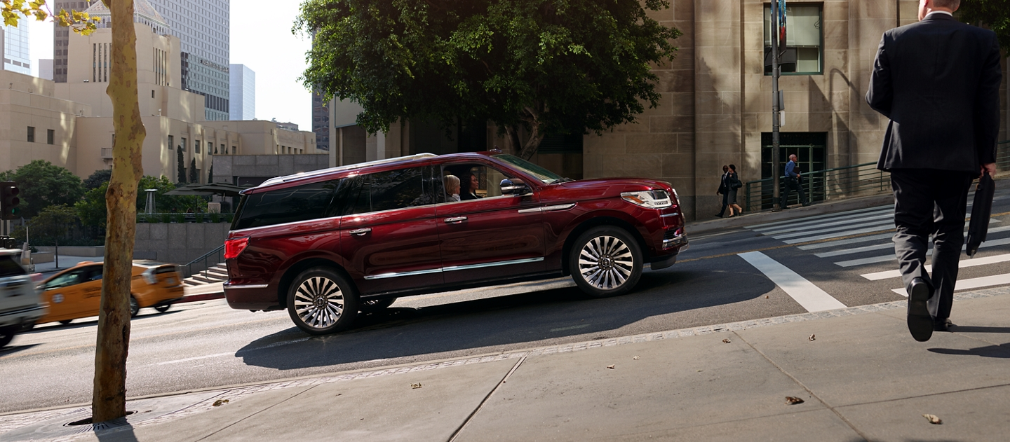 To demonstrate the Auto Hold feature a 2020 Lincoln Navigator is shown at a stop on a steep downtown street alive with the energy of peak daytime