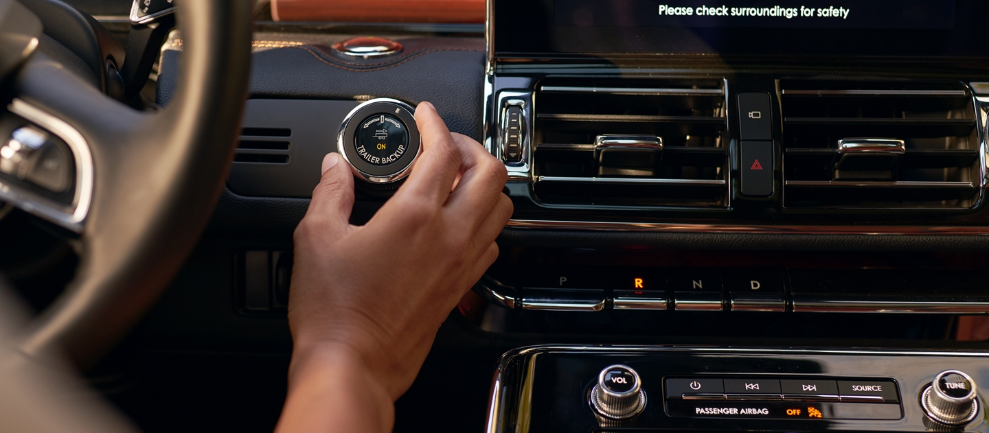 A hand is turning a knob next to the steering wheel of a 2020 Lincoln Navigator equipped with the available Heavy Duty Trailer Tow Package
