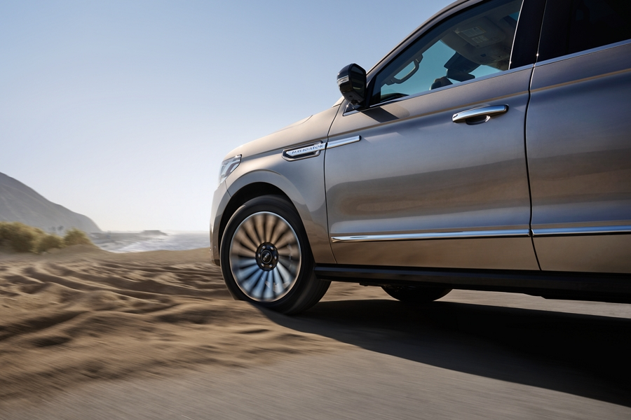 A 2020 Lincoln Navigator with four wheel drive is shown being driven into the sun through loose sand creating bold shadows in the terrain