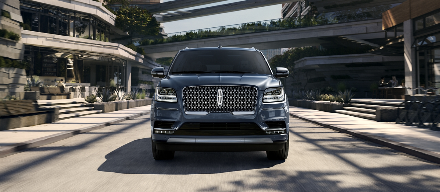 A 2020 Lincoln Navigator in Blue Diamond Metallic is being driven on a freeway against a backdrop of sunlit greenery and a cityscape