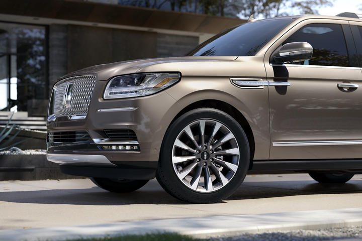The front end of a 2020 Lincoln Navigator in Iced Mocha shows off a twelve spoke wheel design that creates the illusion of fluid movement even in park
