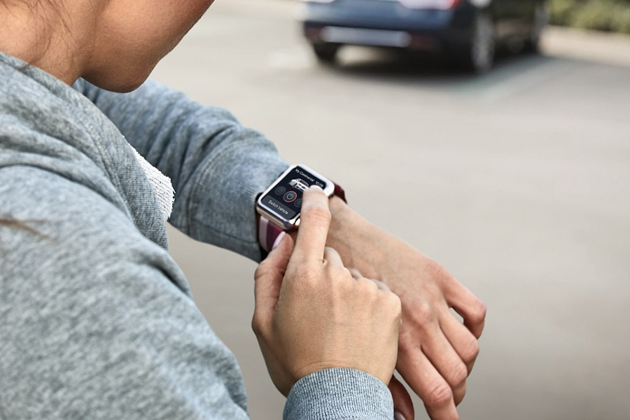 A woman is standing by a car in a parking lot during the day interacting with a smart watch on her wrist using Lincoln Connect
