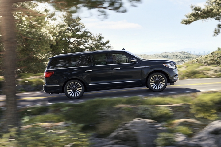A 2020 Lincoln Navigator in Infinite Black is being smoothly guided up an incline surrounded by greenery with a loft and cityscape in the backdrop