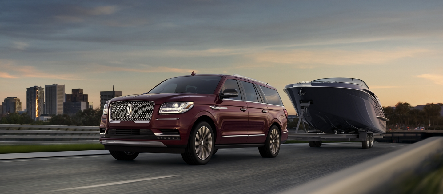 A 2020 Lincoln Navigator extended model is seen towing a large power boat forming an impressive silhouette against a city skyline