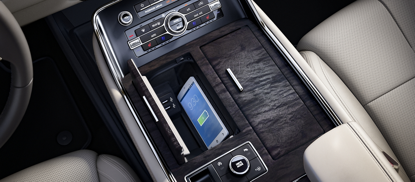 A compatible mobile phone is shown actively charging on the inductive charging system inside a sleek hideaway compartment within the centre console