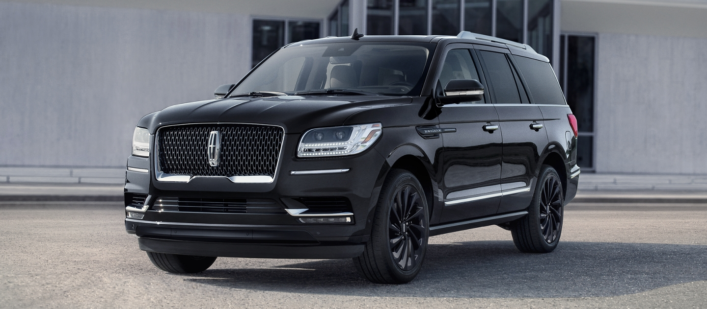 A 2020 Lincoln Navigator Reserve model in the available Infinite Black Monochromatic Package colour shines bright against a grey building backdrop