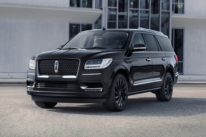 A 2020 Lincoln Navigator Reserve model in the available Infinite Black Monochromatic Package colour shines against a grey building backdrop