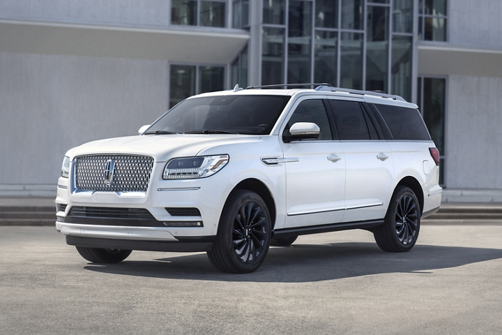 A 2020 Lincoln Navigator Reserve model in the available Pristine White Monochromatic Package parked in front of a building