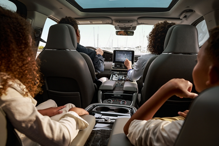 A family is shown comfortably seated in a 2020 Lincoln Navigator with kids in the second row relaxing in spacious captains chairs with split armrests