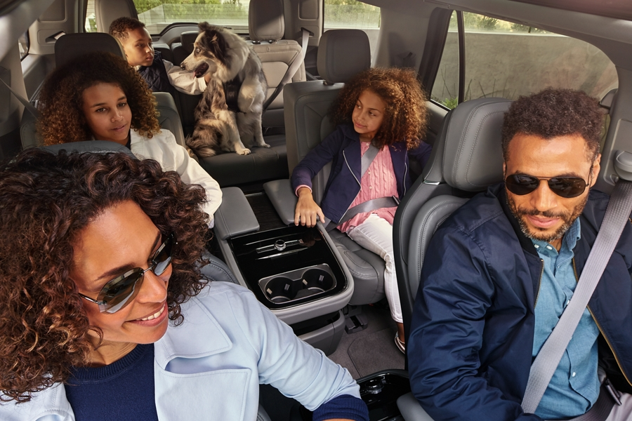 A family of five and their dog look out the window at and enjoy the spacious comfort and open airiness of the 2020 Lincoln Navigator interior