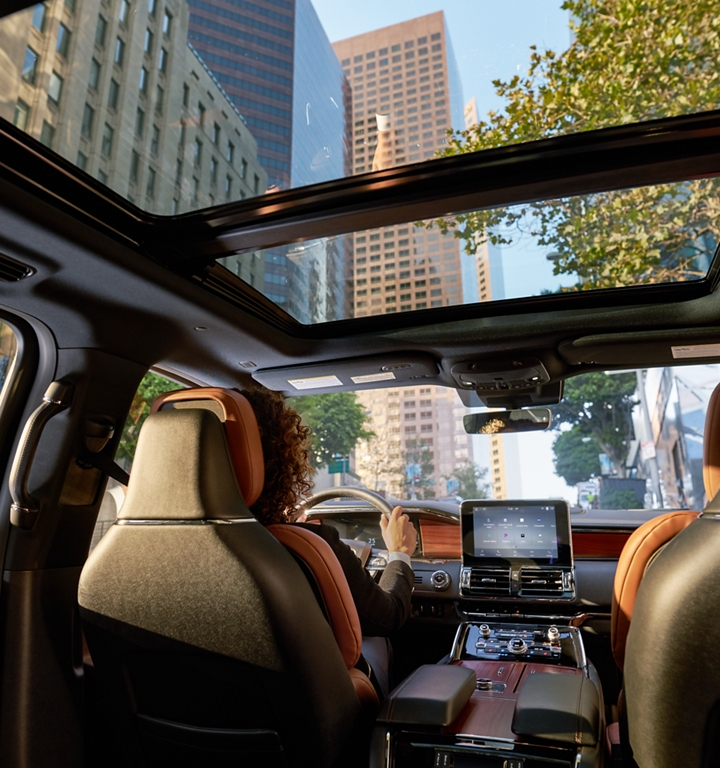 Through the expansive windshield and standard panoramic Vista Roof of a 2020 Lincoln Navigator towering skyscrapers rise against blue skies