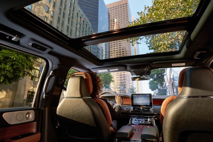 Through the expansive windshield and available standard panoramic Vista Roof of a 2020 Lincoln Navigator towering skyscrapers rise against blue skies