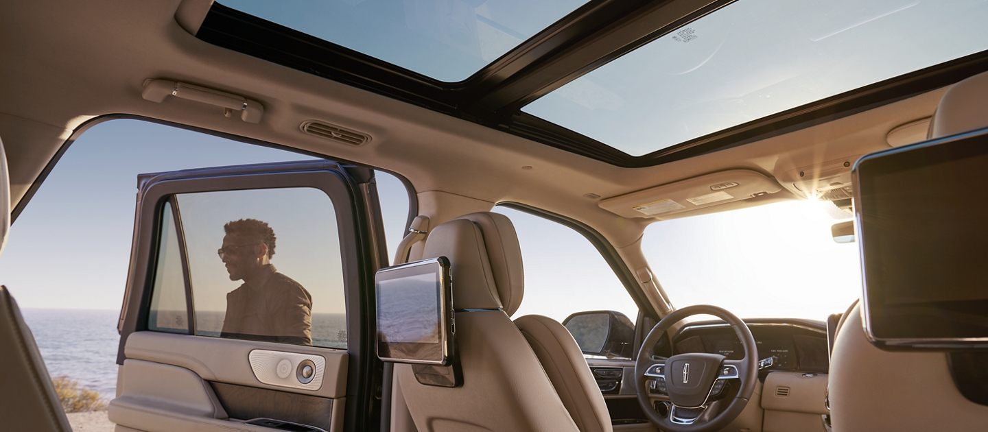 Blue skies are shown through the windows and the Vista Roof as Rear Seat Entertainment screens mounted on the backs of seats reflect the surroundings