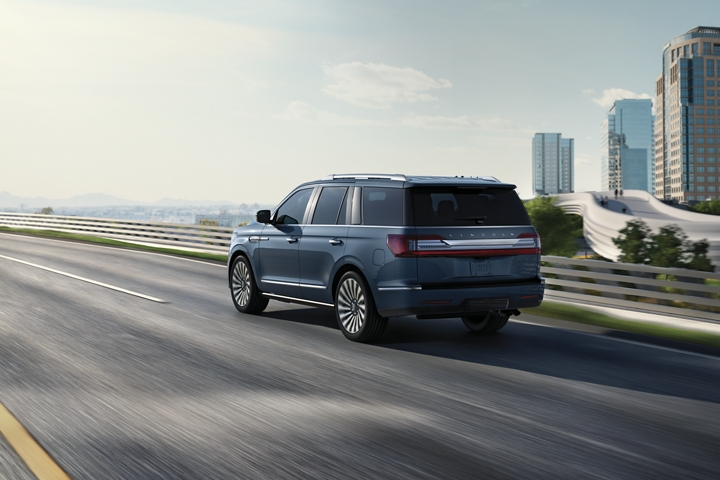A 2020 Lincoln Navigator in Blue Diamond is being driven on a freeway against the blur of sunlit greenery and a cityscape