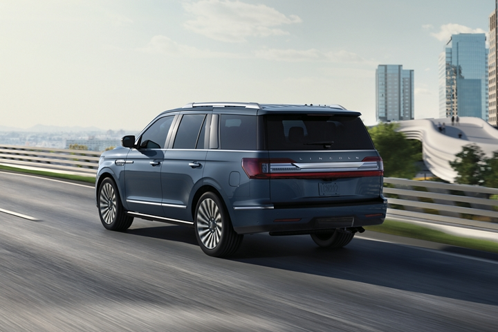 A 2020 Lincoln Navigator is being driven on a highway against a cityscape background demonstrating flexible steering at higher speeds