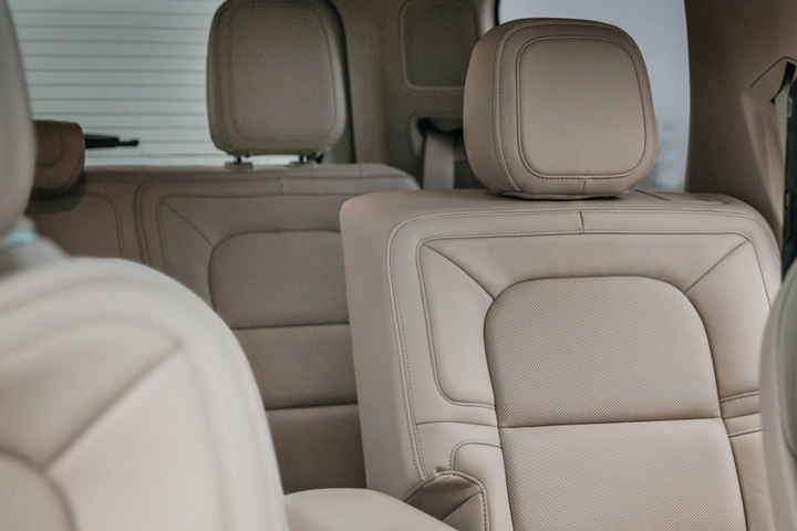 A close up of tan leather trimmed front and second row seats shows off the creamy material and plush design that supports luxury comfort