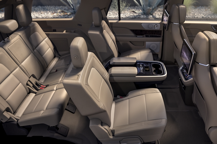 A wide shot of the 2020 Lincoln Navigator interior bathed in soft inviting light shows off the spacious design of the second and third row seating