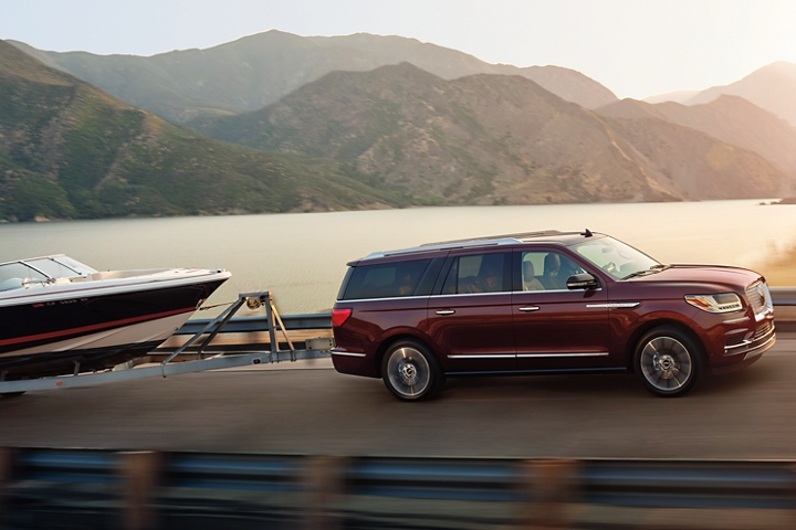 A 2020 Lincoln Navigator in Burgundy Velvet towing a sports boat is being driven up a serene mountain pass with calm waters and warm sunlight