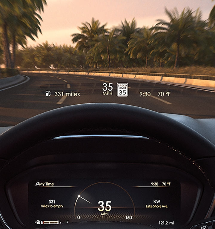 Information is shown being projected on the inside of the windshield via the head up display and there is a road lined with palm trees