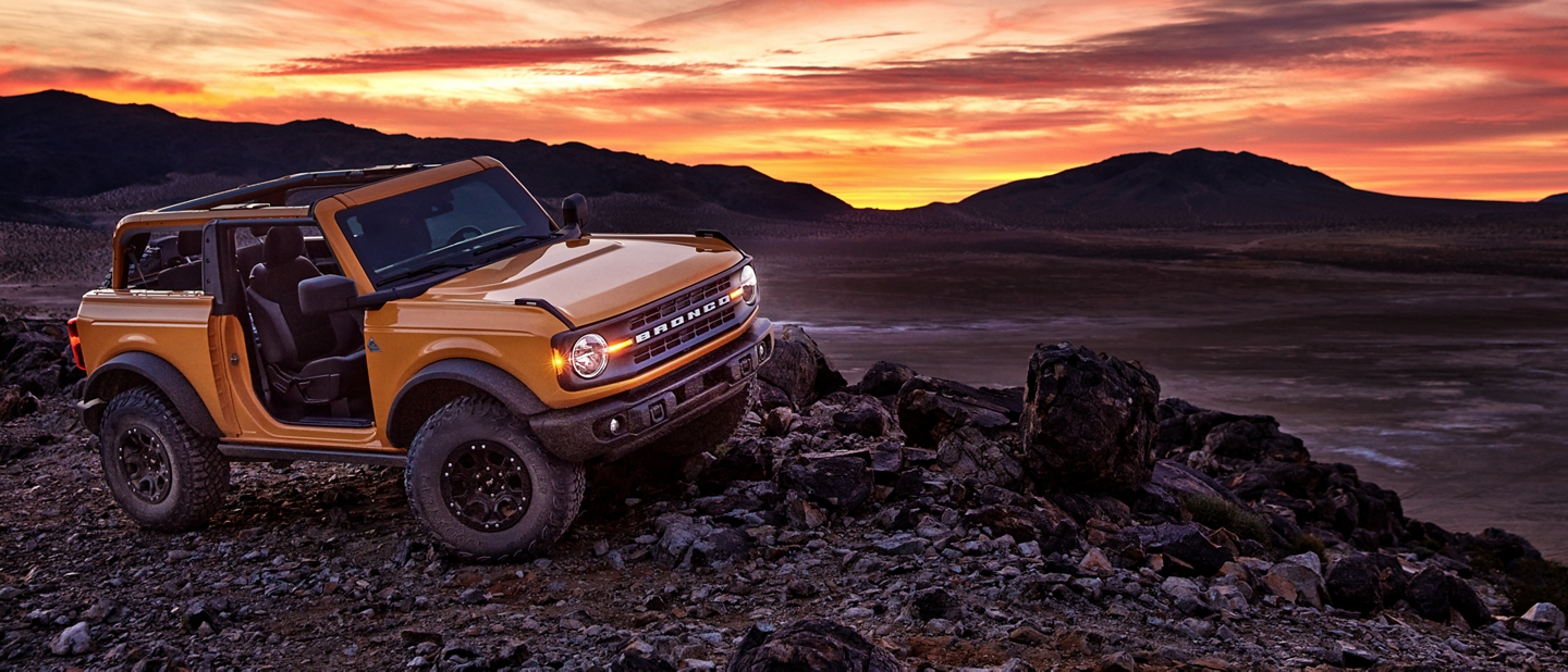 2021 Ford Bronco parked on dark rocks at sunset
