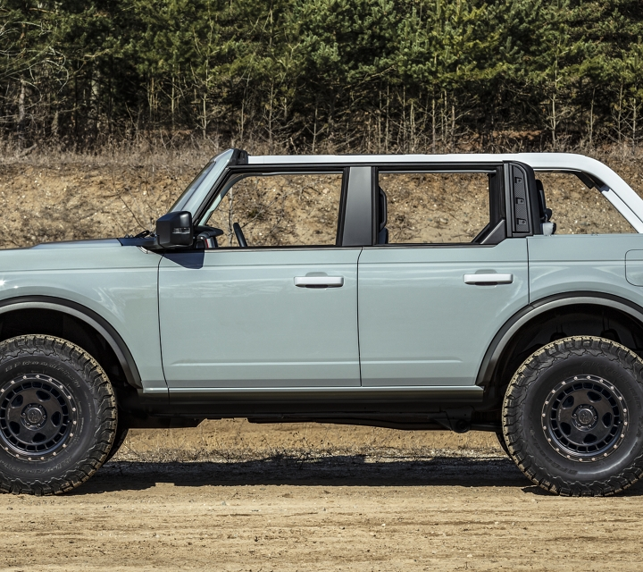 2021 Ford Bronco in cactus gray parked in sandy wooded area