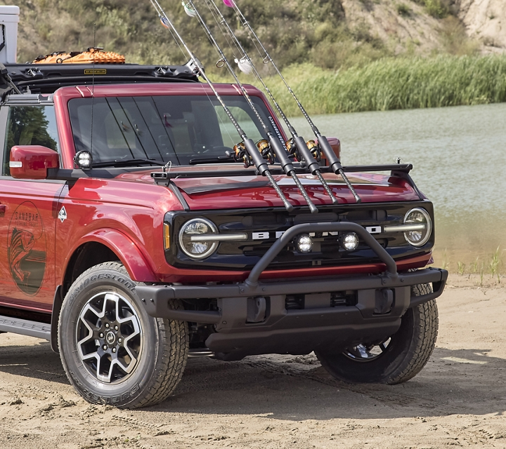 2021 Ford Bronco four door Outer Banks in Rapid Red by a lake with mounted fishing poles and various camping equipment