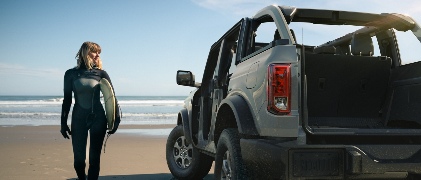 Female Surfer walking next to 2021 Ford Bronco on a beach