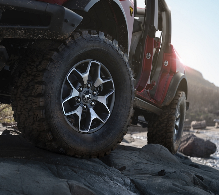 2021 Ford Bronco with available wheels being driven over rocks
