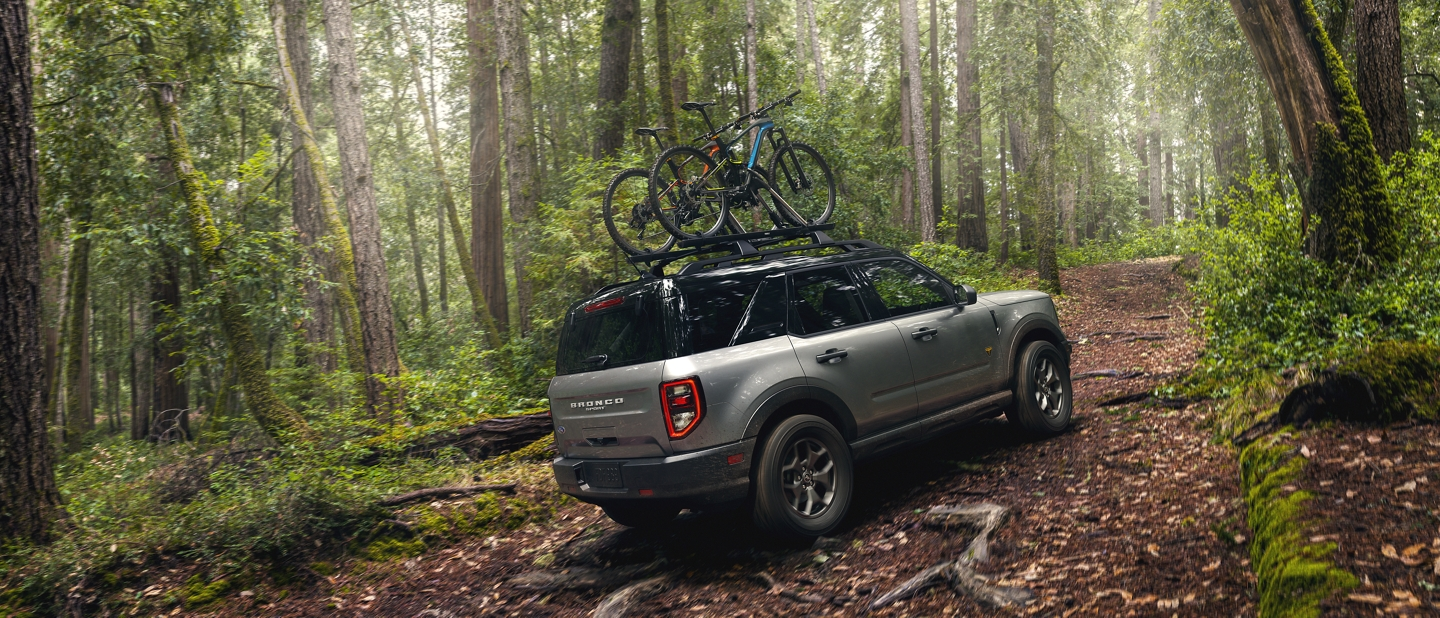 A 2021 Ford Bronco Sport with two bikes on the roof being driven on a wooded trail