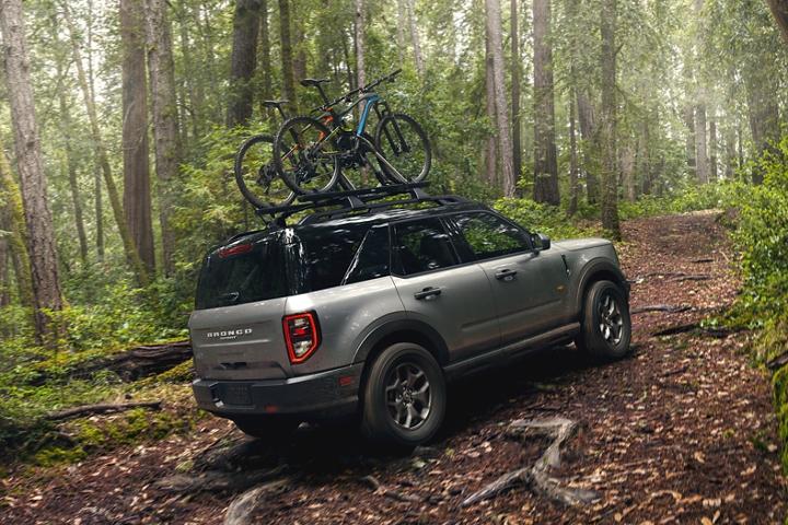 Una Ford Bronco Sport 2021 con dos bicicletas en el techo andando por un camino boscoso
