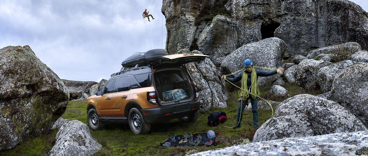 A climber getting their gear ready near a 2021 Ford Bronco Sport